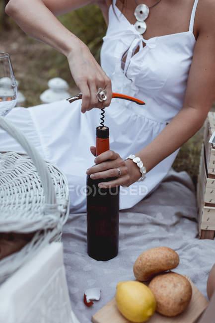 Mulher abrindo garrafa de vinho em um piquenique — Fotografia de Stock