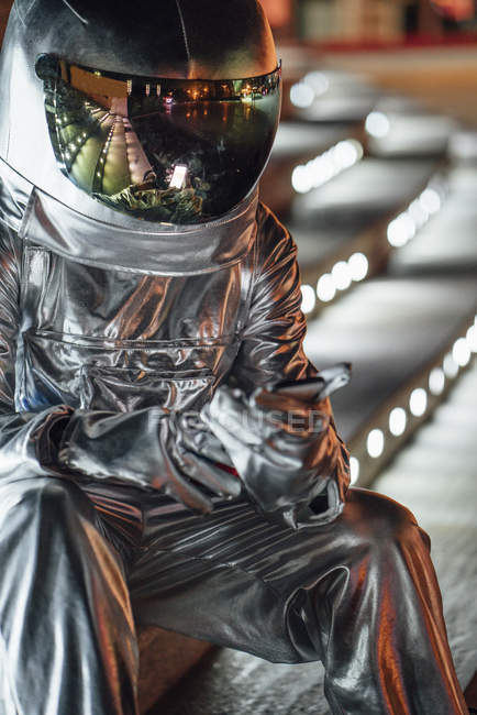 Raumfahrer sitzt nachts auf beleuchteten Treppen und benutzt Handy — Stockfoto
