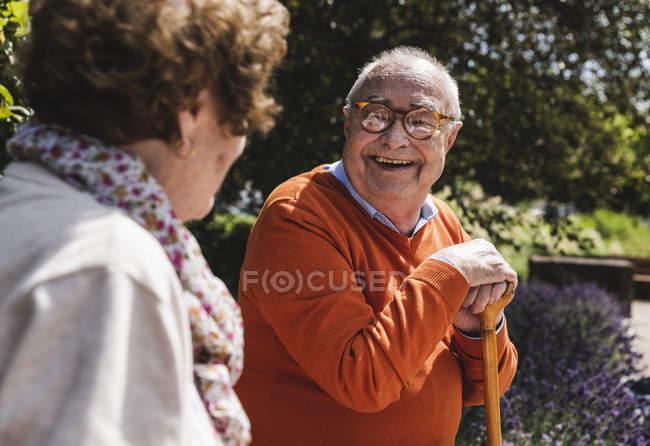 Старшая пара сидит на скамейке в парке и разговаривает — стоковое фото