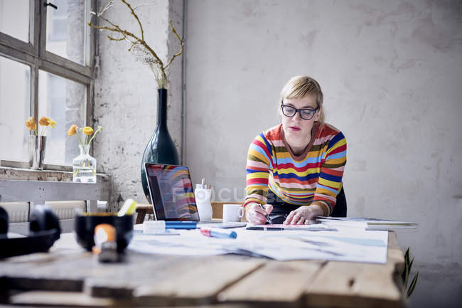 Portrait of young woman working at desk in design loft — Stock Photo