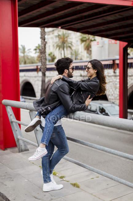 Felice giovane coppia che abbraccia in città — Foto stock