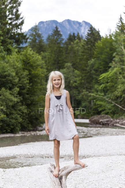 Portrait de fille souriante debout sur du bois mort au bord de la rivière — Photo de stock