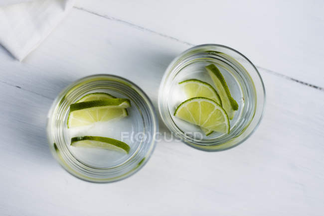 Two glasses of water with sliced limes — стоковое фото