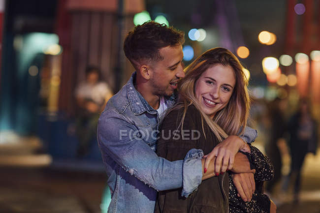 Young couple in love, embracing at a funfair — Stock Photo
