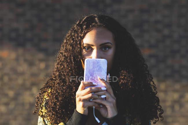 Портрет молодой женщины с вьющимися волосами, держащей мобильный телефон — стоковое фото