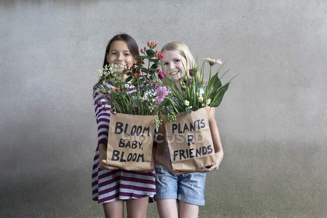 Portrait of two smiling girls standing side by side offering paper bags with flowers — Stock Photo