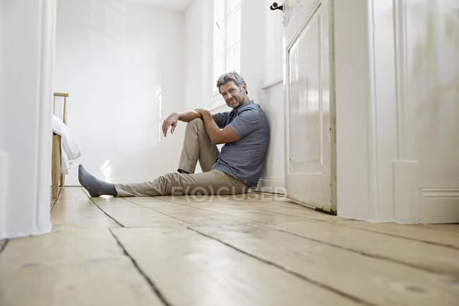 Reife Mann sitzt auf dem Boden des Schlafzimmers, Tagträumen — Stockfoto