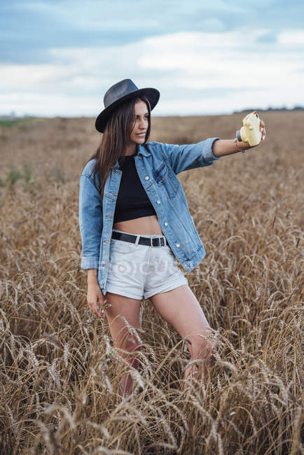 Jovem mulher usando chapéu e casaco de ganga levando selfie com câmera em um campo de milho — Fotografia de Stock