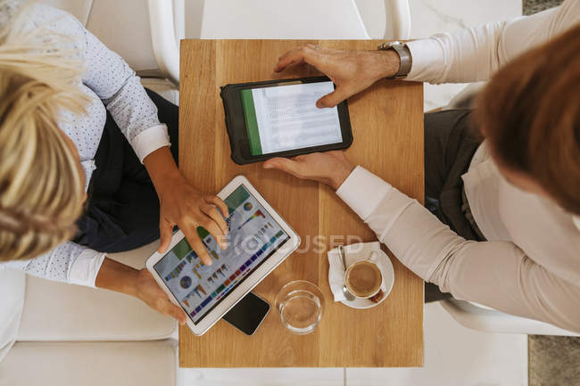 Businessman and businesswoman using tablets in a cafe — Stock Photo