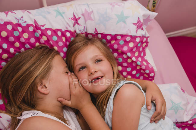 Девочка лежит в постели со своей младшей сестрой и рассказывает секрет. — стоковое фото