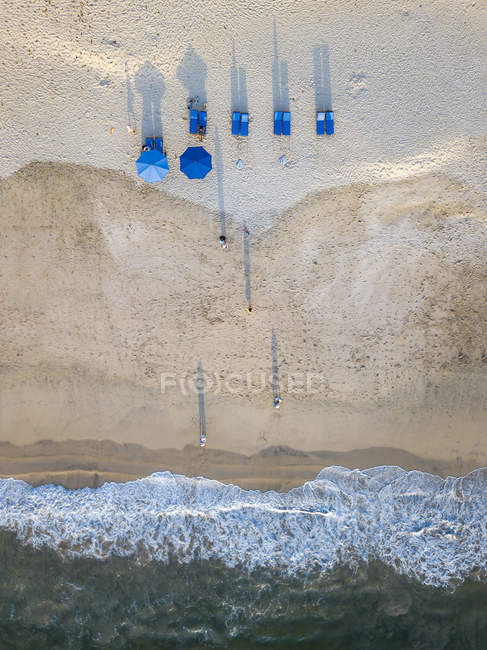 Indonésia, Bali, vista aérea da praia de Jimbaran, das espreguiçadeiras e dos guarda-sóis azuis — Fotografia de Stock