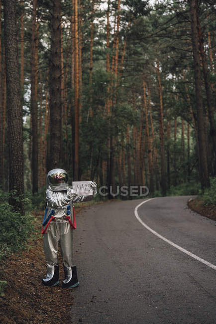 Spaceman hitchhiking to Mars, standing on road in forest — Stock Photo