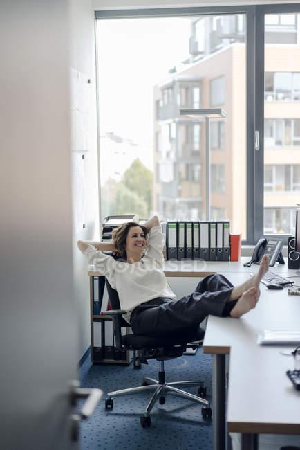 Femme d'affaires se détendre dans le bureau avec les pieds sur le bureau — Photo de stock