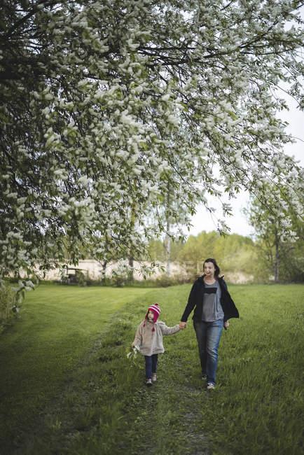 Mutter geht mit Tochter auf bäuerlicher Wiese — Stockfoto