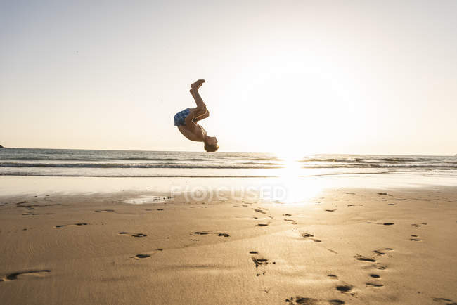 Young man doing somersaults on sandy beach at sunset — Stock Photo