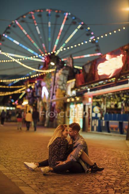 Feliz jovem casal abraçando e beijando em uma feira — Fotografia de Stock