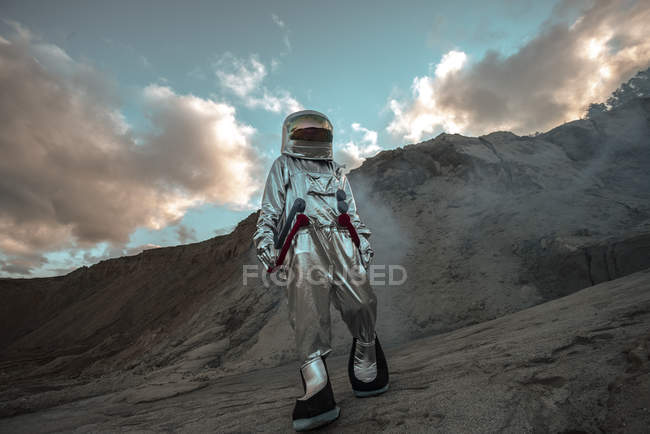 Spaceman exploring nameless planet, walking in dust cloud — Stock Photo