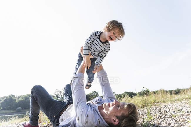 Vater und Sohn amüsieren sich am Flussufer, spielen Flugzeug — Stockfoto