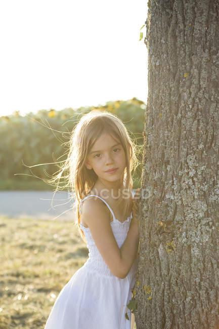 Ragazza in piedi sul tronco albero in estate sera — Foto stock