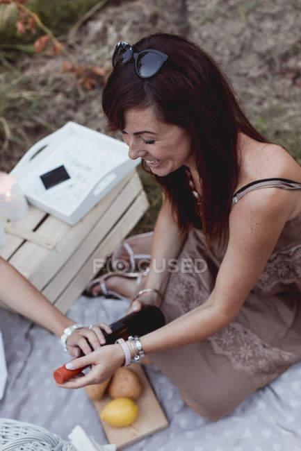 Amici al picnic estivo apertura bottiglia di vino — Foto stock