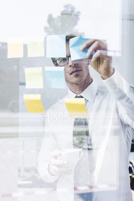 Бизнесмен, прикрепляющий клеевые ноты к стеклянному стеку — стоковое фото