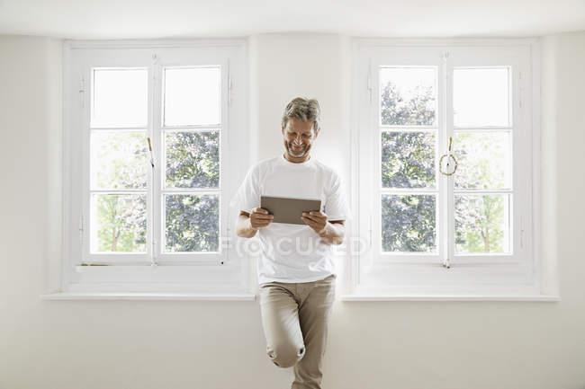 Зрелый человек, стоящий у окна и использующий цифровой планшет — стоковое фото