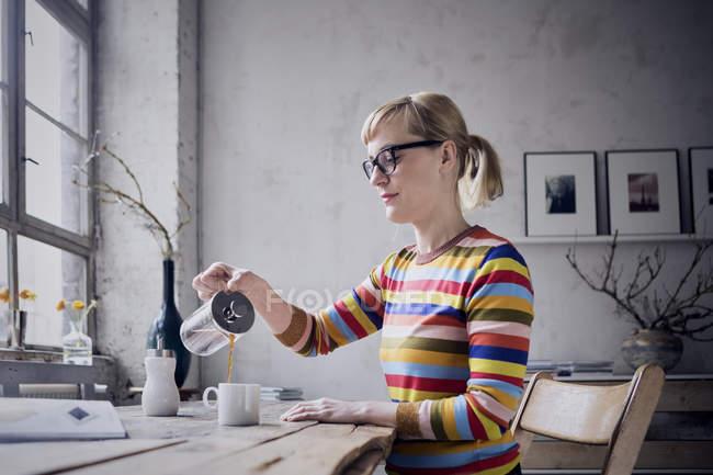 Frau gießt Kaffee in Becher auf Schreibtisch im Dachgeschoss — Stockfoto