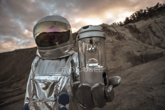 Spaceman exploring nameless planet, holding analyzer — Stock Photo