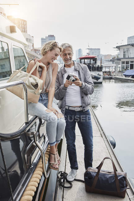 Man and young woman with age difference with camera on jetty next to yacht — Stock Photo