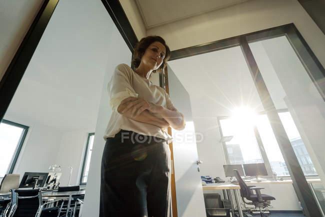 Geschäftsfrau im Amt, die Arme verschränkt, den Blick nach unten gerichtet — Stockfoto