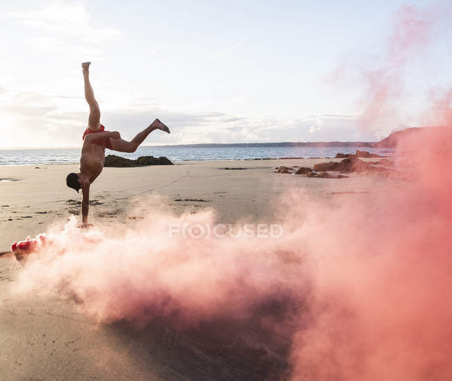 Man doing movement training at beach with red smoke — Stock Photo