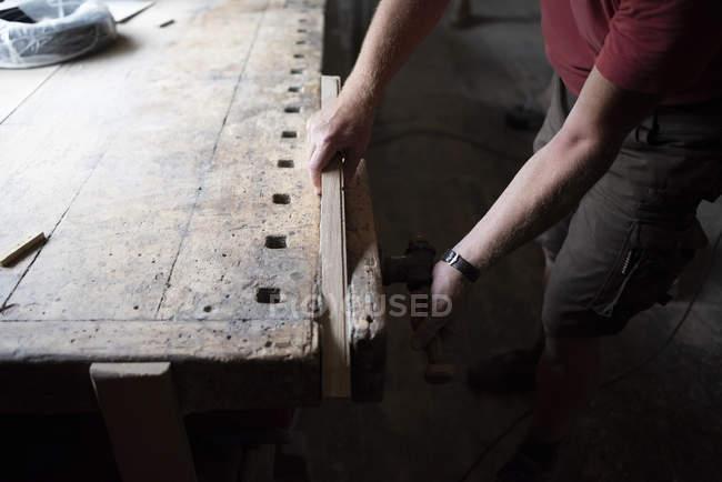 Nahaufnahme eines Tischlers, der ein Stück Holz in der Werkstatt einspannt — Stockfoto