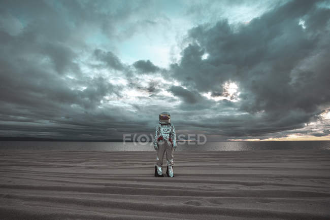 Spaceman standing alone at lake on nameless planet — Stock Photo