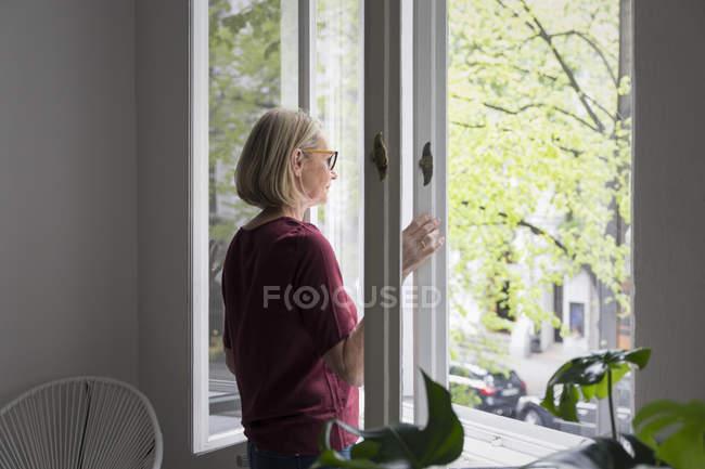 Зрелая женщина у окна дома — стоковое фото
