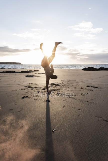 Man doing movement training at beach at sunset — Stock Photo