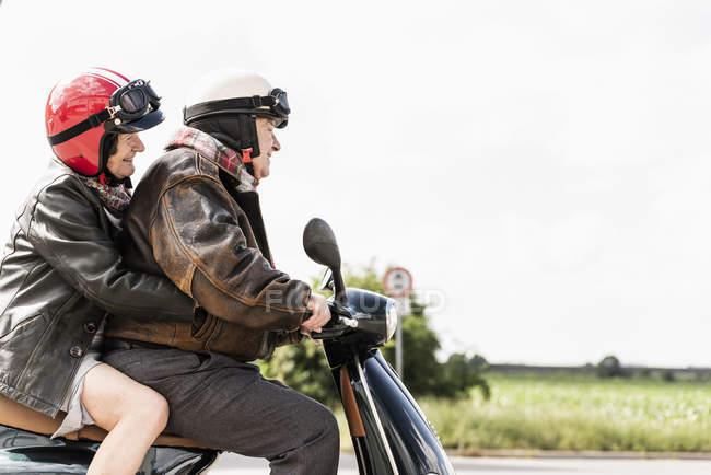 Щасливий старший пара їзда моторолер на країновому шляху — стокове фото