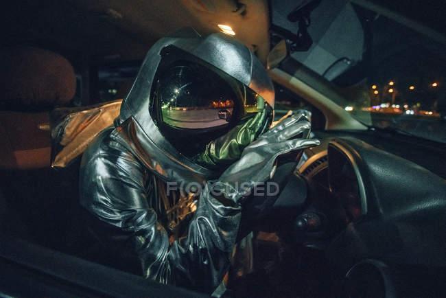 Primer plano del astronauta sentado en el coche por la noche - foto de stock