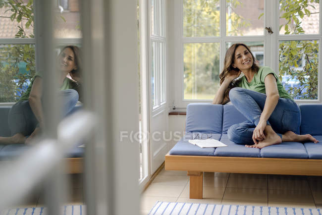 Portrait of smiling mature woman sitting on couch at home — Stock Photo