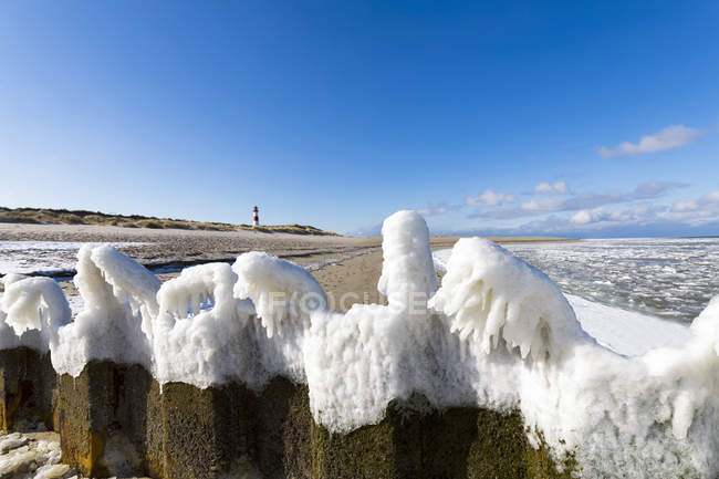 Germany, Schleswig-Holstein, Sylt, beach, frozen breakwater and lighthouse in winter — Stockfoto