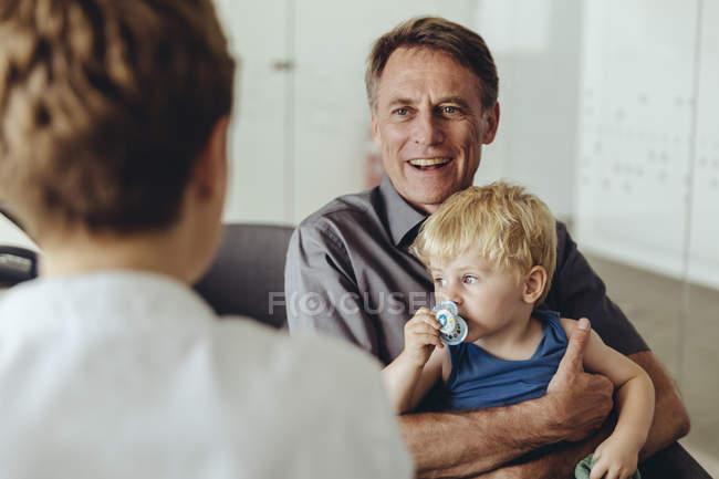 Батько і син радилися з педіатром. — стокове фото