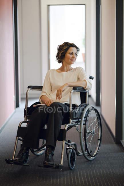 Mulher de negócios com deficiência sentada em cadeira de rodas no escritório e olhando para longe — Fotografia de Stock