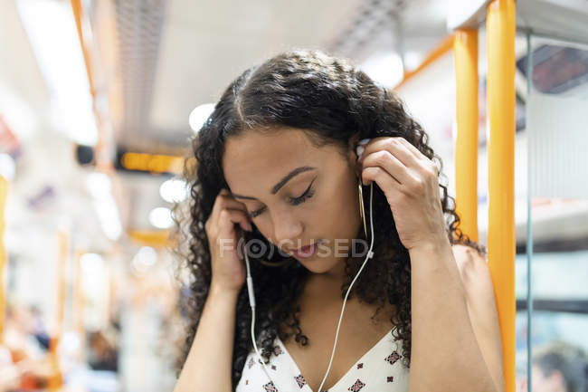 Young woman listening to music with earphones in subway train — Stock Photo