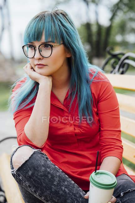 Porträt einer jungen Frau mit gefärbten blauen Haaren, die mit Getränken auf einer Bank sitzt — Stockfoto