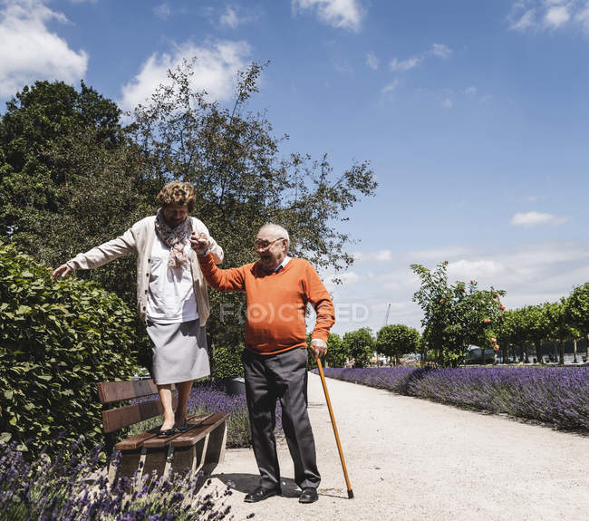 Старший пара веселяться в парку, старший чоловік допомагає жінці баланс на лавці — стокове фото
