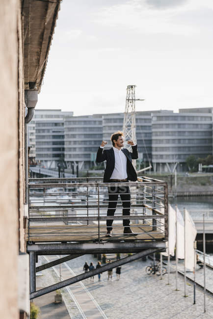 Businessman standing on balcony in city and flexing muscles — Foto stock