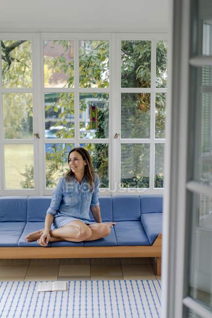 Sorrindo mulher madura sentada no sofá em casa — Fotografia de Stock