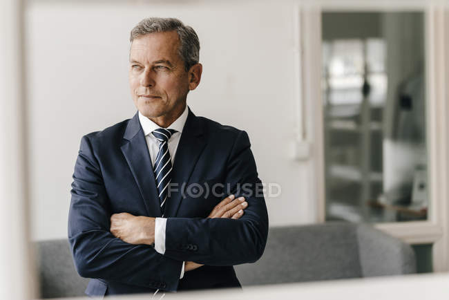 Portrait of mature businessman with arms crossed in office — Stock Photo