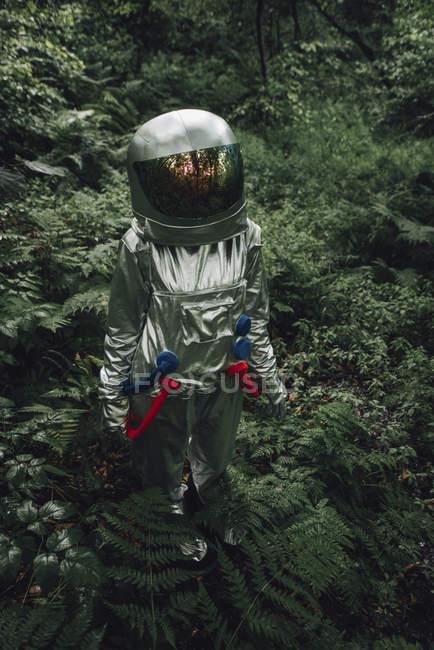 Spaceman explorar la naturaleza, examinar las plantas en el bosque - foto de stock