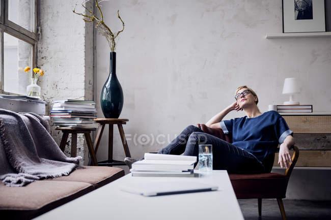 Pensive woman sitting on armchair in loft looking up - foto de stock