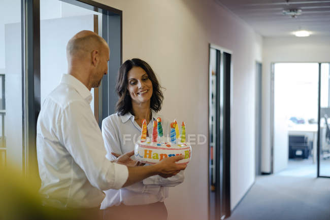 Businessman gifting his colleague with a birthday cake in office — Stock Photo